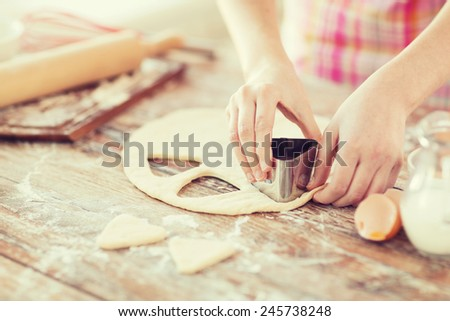 cooking and home concept - close up of female hands making cookies from fresh dough at home - stock photo