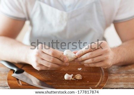 cooking and home concept - close up of male hands taking off peel of garlic on cutting board - stock photo