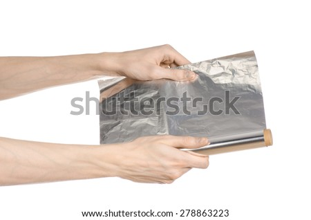 Cooking and shisha topic: human hand holding a foil isolated on white background in studio