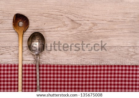 Cooking and silver spoon on a checkered table cloth and wooden board - stock photo