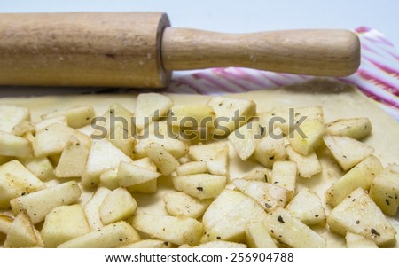 cooking apple strudel at home: the dough, rolling pin and apple slices - stock photo