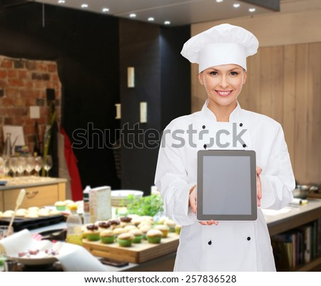 cooking, bakery, people, technology and food concept - smiling female chef, cook or baker showing tablet pc computer blank screen over restaurant kitchen background - stock photo