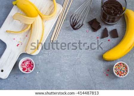 Cooking Banana Pops - bananas, dark chocolate, sweet sprinkling and cutting board, gray concrete background, space for text