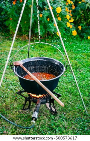 Cooking beef goulash soup in a cauldron. Cooking lunch in a natural environment in a pot on an open fire.
