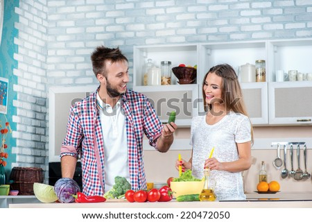 Cooking best homemade salad. Young and beautiful enamored couple cooking vegetables and help each other while breakfast is prepared with vegetables in the kitchen. - stock photo