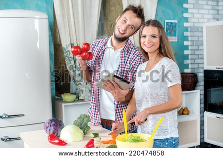 Cooking  Best salad recipe. Young and beautiful couple in love food cooking according to the recipe on the tablet while they are preparing breakfast in the kitchen. - stock photo