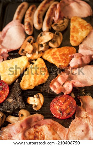 Cooking breakfast for a family with a closeup overhead view of bacon, hash browns, sausages, tomato and mushrooms sizzling on a hot griddle - stock photo