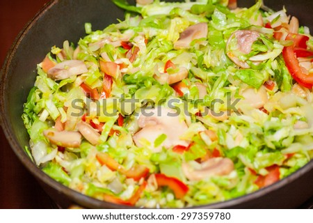 Cooking cabbage with mushrooms in fried pan - stock photo
