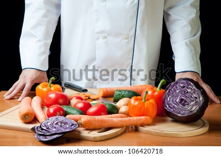 Cooking: chef standing by the kitchen table with variety of vegetables - stock photo