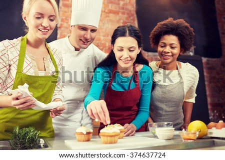 cooking class, culinary, bakery, food and people concept - happy group of women and male chef cook baking in kitchen - stock photo
