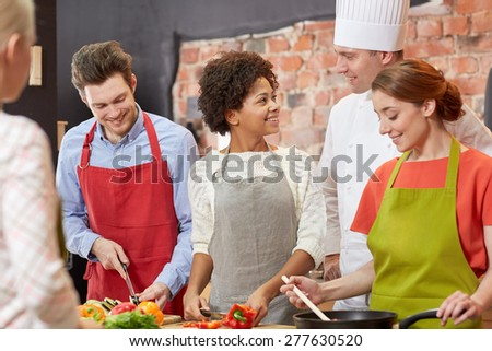 cooking class, culinary, food and people concept - happy group of friends with male chef cook cooking and talking in kitchen - stock photo