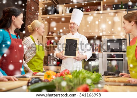 cooking class, culinary, food and people concept - happy women and chef cook with blank menu chalk board in kitchen over snow effect - stock photo