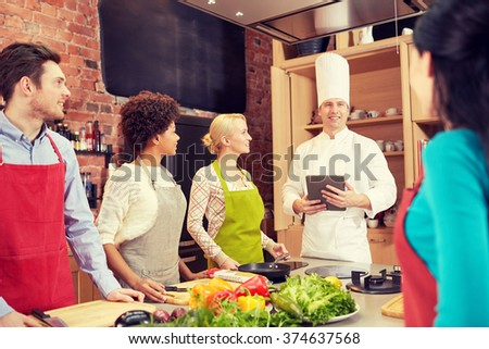 cooking class, culinary, food, technology and people concept - happy friends with tablet pc in kitchen - stock photo