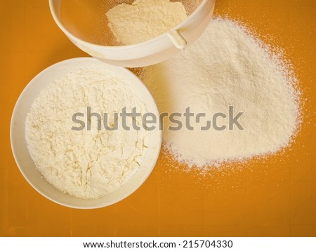 Cooking concept. Preparation for baking, bake ingredients and kitchen tools to make a cake, sifting wheat flour on orange nonstick silicone mat, top view