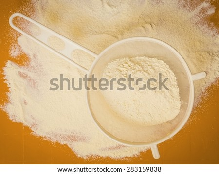 Cooking concept. Preparation for baking, bake ingredients and kitchen tools to make a cake, sifting wheat flour on orange nonstick silicone mat, top view - stock photo