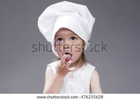 Cooking Concepts and Ideas. Portrait of Lovely Cute Caucasian Girl Posing as Cook. Against Gray Background. Horizontal Image