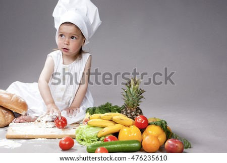 Cooking Concepts. Little Caucasian Girl Posing as Cook with Vegetables. Against Gray Background. Horizontal Image