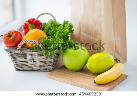 cooking, diet, vegetarian food and healthy eating concept - close up of basket with fresh ripe juicy vegetables, greens and fruits on kitchen table at home - stock photo