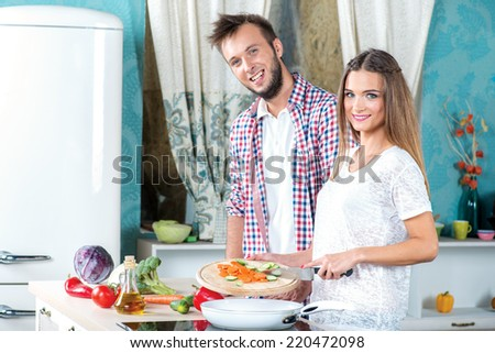 Cooking dinner together. Attractive loving couple is cooking meal while standing in the kitchen. A girl holding a knife and throws vegetables in a frying pan