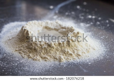 Cooking dough for Italian pasta, heap with a hole of water, mixing - stock photo
