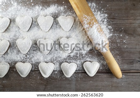 Cooking dumplings. Raw heart shaped dumplings, flour and rolling pin on wooden background. Top view. - stock photo