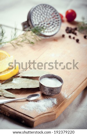 Cooking fish: kitchen utensils, spices and herbs for cooking fish, on wooden cutting board, with space for text - stock photo