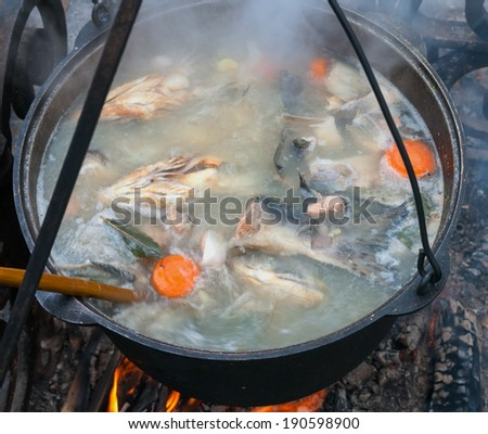 cooking fish soup in a pan on the fire - stock photo