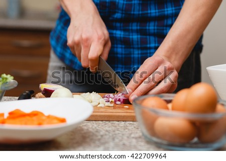 cooking, food and home concept - close up of male hand cutting vegetables on cutting board at home
