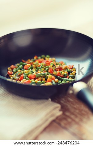 cooking, food and home concept - close up of wok pan with vegetables - stock photo