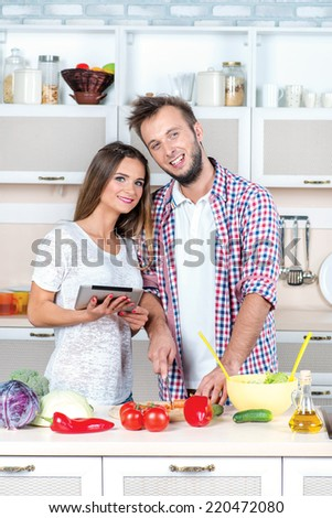 Cooking food for lovers. Young and beautiful couple in love cooking food according to the recipe on the tablet while they are preparing breakfast in the kitchen - stock photo