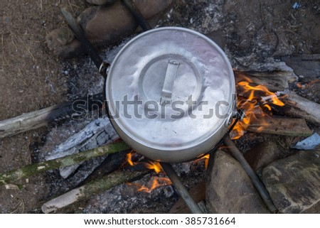 Cooking food using firewood on campfire at forest camping ground during weekend. - stock photo