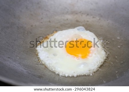 cooking fried egg in hot pan with oil - stock photo