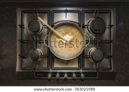 Cooking fusilli pasta in boiling water in a metal pan on a stove - stock photo