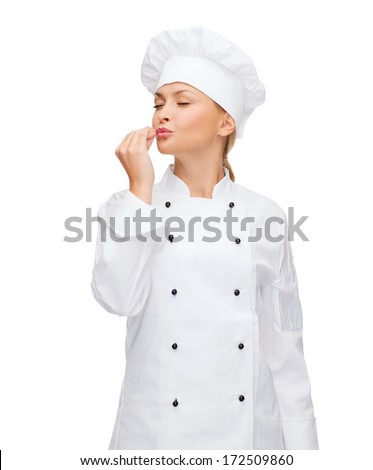 cooking, gesture and food concept - smiling female chef showing delicious gesture