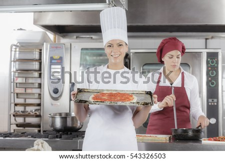 Cooking gourmet pizza in an professional industrial restaurant kitchen