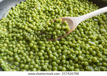 cooking green peas in black frying pan with wooden spoon, stewed vegetables with onion and others herbs - stock photo