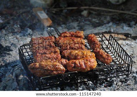 Cooking grilled minced meat balls on fire . - stock photo