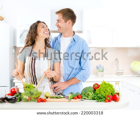 Cooking. Happy Couple Cooking Together - Man and Woman in their Kitchen at home Preparing Vegetable Salad.Diet. Dieting. Healthy Food concept. Dinner. Vegan food - stock photo