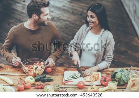 Cooking healthy. Top view of beautiful young couple preparing healthy salad together and smiling - stock photo
