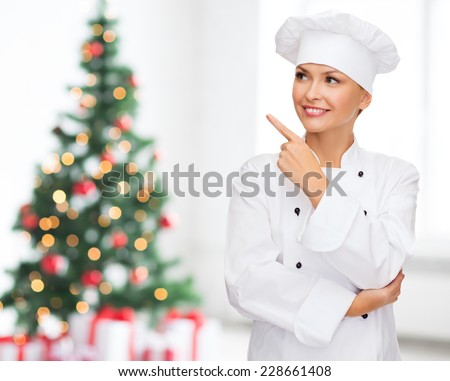 cooking, holidays and people concept - smiling female chef, cook or baker pointing finger up over living room and christmas tree background - stock photo