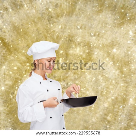 cooking, holidays, people and food concept - smiling female chef with pan and spoon mixing food over yellow lights background - stock photo