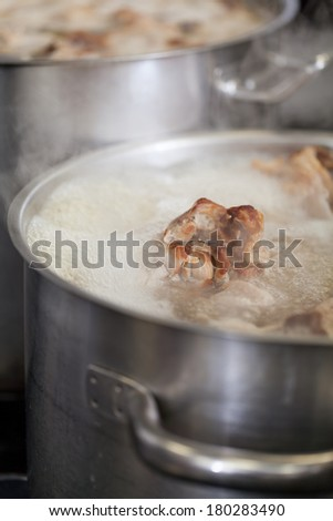 Cooking in a commercial kitchen with large stainless steel pots filled with stew and vegetables on a central gas hob - stock photo