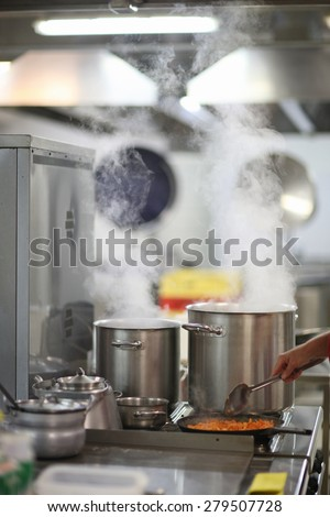 Cooking in a restaurant kitchen, steam over cooking pots - stock photo