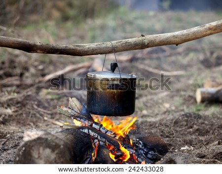 Cooking in sooty cauldron on campfire at forest - stock photo