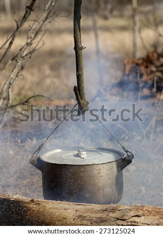Cooking in sooty cauldron on campfire at spring forest - stock photo
