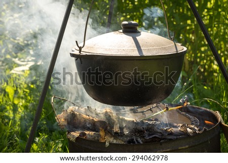 Cooking in the cauldron on fire - stock photo
