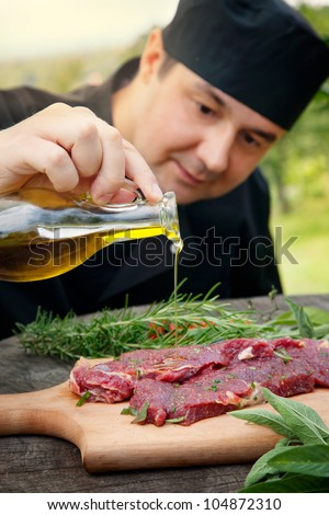 Cooking ingredients: marinated meat,oil,vinegar, herbs and vegetables - stock photo