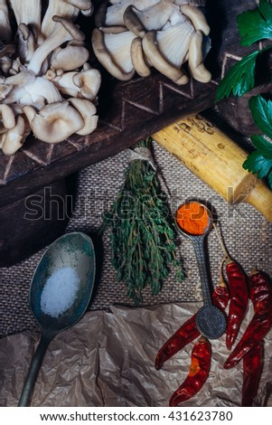 Cooking ingredients - mushrooms, spices arranged at the rustic wooden table