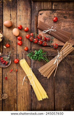 Cooking ingredients. Pasta with ingredients. Tomatoes, spaghetti, eggs and herbs - stock photo