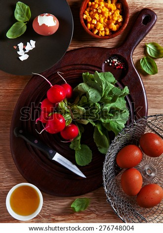 cooking Ingredients: radishes, eggs, corn. Preparation of light summer salad. - stock photo
